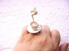 This is soooo cute! There is a cup of tea with cream being poured! Very kawaii!        It is on a silver tone adjustable band that will fit most