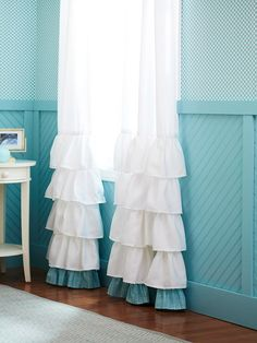 DIY ruffle curtains: Buy three curtain panels, use the extra one to add ruffles to the bottom of each panel, then add a contrasting ruffle to the very bottom.
