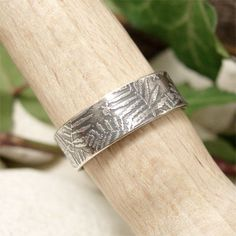 Sterling silver ring delicately embossed with unfurled fern fronds echoing the shadowy forest floor A beautiful nature inspired ring. Hand forged from sheet sterling silver that has been delicately textured with my own unique fern fronds texture, the listing photos show a medium width band