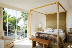 Architect and designer Daniel Romualdez designed this Los Angeles master bedroom's gilded four-poster bed; its headboard is upholstered in Cavallini cowhide by Edelman Leather, and the linens are by Frette.