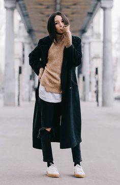 Street style look blusa canelada marrom, calça preta rasgada, tênis branco e sobretudo preto.