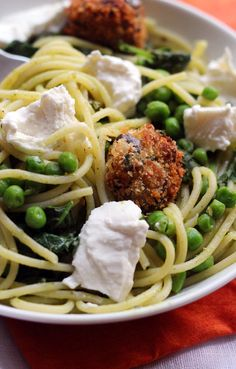 Spaghetti and meatballs goes green for spring! This recipe for spaghetti with eggplant balls, pesto, peas, and greens makes the perfect Sunday supper OR weeknight meal.