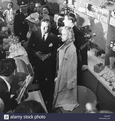 Download this stock image: American actress Marilyn Monroe and Sir Laurence Olivier seek refuge from the waiting photographers behind a counter at Heathrow Airport. Monroe had just flown into London with her husband, playwright Arthur Miller who is pictured behind with Vivien Leigh - ENHJF8 from Alamy's library of millions of high resolution stock photos, illustrations and vectors.