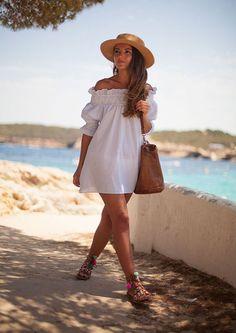Une robe blanche à épaules dénudées avec des sandales à pompons