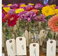 Guests find their seating assignments on tags attached to small milk bottles filled with colorful dahlias.