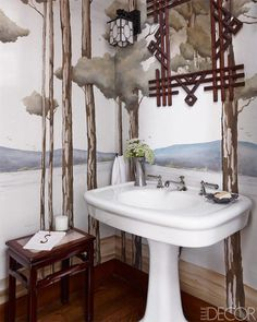 A mural by Jean Horihata in a powder room; the circa-1890 Tramp Art mirror is American, the stool is Chinese, and the sink fittings are by THG.