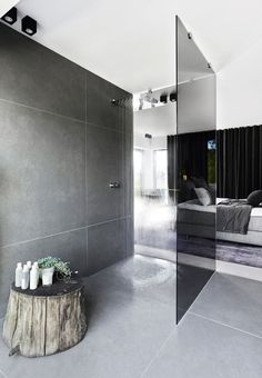 Grandiosely shower head with a 'rainy-feeling' together with a tree stump gives a touch of nature in this modern bathroom.