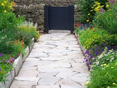Rose Cottage, the oldest building in Greenfield Village was imported from England's Cotswold Hills to represent the area from which Henry Ford's ancestors immigrated. It is surrounded by a lush country garden. This stone path leads to the barnyard.