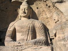 Two Buddhist statues. The cave front has collapsed, leaving them visible from outside. Yungang Grottoes, near Datong, Shanxi province, China. (Felix Andrews) Wikipedia