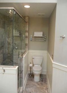 bathroom remodel, travertine marble, pedestal soaker tub, glass shower enclosure, black chandelier, double vanity with black counter top