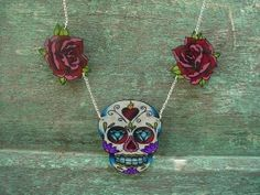 hand painted on hard cut plastic (clear plastic so its double sided!) it is a sugar skull with a rose on each side. when its on it looks like a mini chest piece tattoo.. a really awesome piece of art. the skull has a sacred heart, diamonds, flowers and filigree on it and measures 2 inches tall and and 1.5 inches across, the roses are blood red and pink and measure 1 inch by 1 inch, and it all hangs from a silver plated chain, closes with a spring ring and measures 20 inches around.