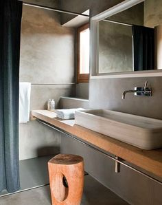 Concrete grey masculine and earthy bathroom with simple timber vanity with an above counter rectangle basin sink and timber tree stump stool, very minimalist design