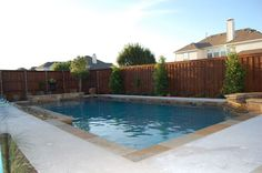 Classic pool design with clean, simple lines, natural stone border, raised stone fountain and spa  By Outdoor Signature in Argyle, TX