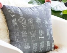 Enjoy the prickly goodness of desert succulents with this darling boho throw pillow. The front is screen printed by hand with bright white, earth-friendly ink onto sumptuous ecru colored linen fabric. It's paired on the back with a crisp, durable natural cotton, and the pillow corners are accented with soft, fluffy, pacific blue pom poms.  The removable cover closes with a hidden zipper, and comes with the downy insert, so you can start cozying up as soon as you receive it. • Includes pillow…
