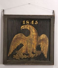 "Polychrome Painted Eagle Wooden Trade Sign, America, c. 1845, double-sided square sign centered with a gilt painted eagle clutching arrows above ""1845"" on a black ground, molded wood frame with iron hardware, (scattered paint wear, joinery separation), total ht. 48 1/2, wd. 43 3/4 in.   Sold for $ 7,638"