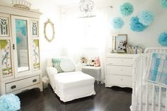 Gorgeous nursery design with light gray walls paint color, white vintage crib, white vintage chest, vintage mirrored armoire, white chaise lounge, gold ornate mirror, blue pom poms and espresso stained wood floors. decorpad.com
