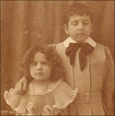 In the Victorian era, when people died, their family would have their dead body posed for a picture to remember them by. The boy in this picture was the girl's brother's dead body, held up straight with certain clamp things.