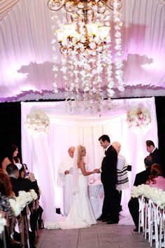 Wedding ceremony with ceiling drape, uplighting, orchids hanging from chandelier, pink, lavender.  By Diana Gould Ltd.  Photo by Brian Ambrose Photography.