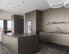 Gerade Linien, schlichte Formen, eine minimalistisch wirkende Küche in perfekter Harmonie mit der Umgebung. Das metallisch matte Glänzen der bulthaup b3 Aluminium Fronten in sandbeige unterstreicht die edle Optik. Um die Freiheit des hohen Raumes nicht zu stören kommt ein BORA Professional System zum Einsatz.