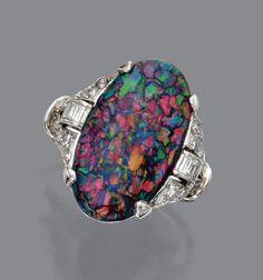 Black opal and diamond ring, circa 1920 - Sotheby's. The oval-shaped black opal measuring approximately 20.5 by 11.2 by 4.9 mm., the sides accented with buckle motifs set with single-cut and baguette diamonds, mounted in platinum, size 7¾.