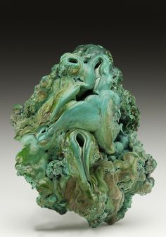 A convoluted-botryoidal old-time specimen of Malachite from the Schwaz area in Austria. The Malachite has the overall appearance of stalactitic dripstone surface over a more cellular interior, with light blue Chrysocolla, and minor black-brown Fe-oxides.