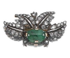 EMERALD AND DIAMOND BROOCH, BUCCELLATI, 1930S.  Of foliate design, the central oval cabochon emerald within surrounds of rose-cut diamond leaves, signed Buccellati.