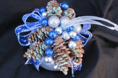 Silver ornament decorated with pinecones, berries and ribbons