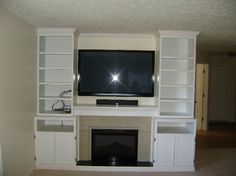 custom built in. entertainment center with shelves and storage. this would look great around a fireplace too
