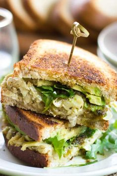 """Chunky white beans, artichoke hearts and creamy avocado slices are drizzled with garlicky pesto sauce, stuffed between bread slices and grilled until golden and delicious to create this comforting and flavorful vegan green goddess melt sandwich. Let's just look past the fact that I named this a """"melt sandwich"""" but nothing is technically melting here. […] Vegan Recipes Beginner, Recipes For Beginners, Delicious Vegan Recipes, Healthy Recipes, Tasty, Yummy Food, Vegan Mozzarella, Vegan Pesto, Vegan French Onion Soup"""