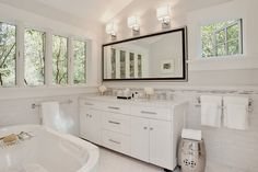 """A bathroom is the perfect space for a multitude of whites. Easily cleaned and giving the space a fresh feel, white towels and accessories perfectly blend into spa-like white surroundings. One solid frame of deeper color around the mirror is all the contrast this room needs. The """"silence"""" of the room allows you to focus on the framed views of the trees outdoors."""