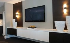 tv wall | TV wall with floating storage cabinet and light sconces on a textures ...