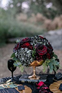 Blood-red 'Black Baccara' roses, black hydrangeas, and seeded eucalyptus in a gold compote | Photo by Sweet Blooms Photography