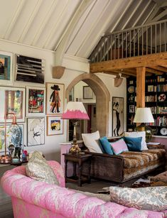 Originally the main classroom, this area has been transformed into a relaxed space furnished with an eclectic mix of pieces, including a leopard-print bergère sofa and pink patterned Chesterfield.