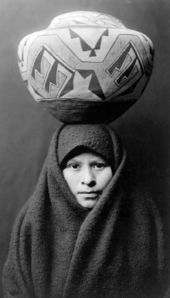 """""""Zuni girl with jar"""" A girl of the Zuni tribe, headcarrying a Native American pottery jar, in New Mexico. Head-and-shoulders portrait, from The North American Indian, by Edward S."""