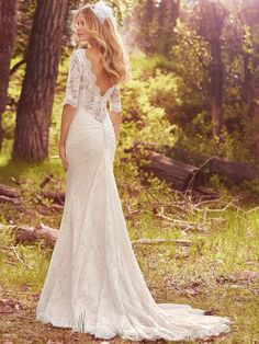 Maggie Sottero - MCKENZIE, This demure fit-and-flare wedding dress features allover lace, with sheer lace comprising the elbow-length sleeves, classic bateau neckline, and V-back for a touch of alluring romance. Lined with Inessa jersey for a lightweight feel. Accented with back ruching and scalloping along the hem and neckline. Finished with covered buttons over zipper closure.