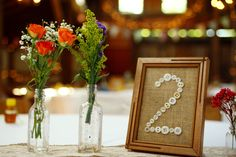 our wedding centerpieces... button and burlap table numbers.. wildflowers in old glass jars... landis valley museum