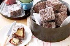 The Lamington was originally invented as a way to use cake that was a few days old. If you're using fresh baked cake ... the trick is to freeze the cake first to prevent the it falling apart while you coat it. ;)