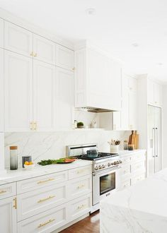Stunning white kitchen boasts white cabinets with brass pulls featuring white and gray marble countertops joining with a matching backsplash, a white wood panel range hood and a marble floating spice shelf underneath.