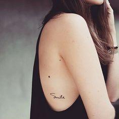 Tatuaggi piccoli donne, scritta Smile sulla schiena di una ragazza giovane