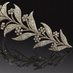 A Georgian diamond tiara, circa 1800 Designed as a spray of myrtle, each pair of leaves pavé-set with cushion-shaped and old brilliant-cut diamonds, the flowerheads collet-set with similarly cut stones, mounted in silver and gold, diamonds approximately 25.00 carats total, detachable to be worn either as a single corsage ornament or two smaller brooches, fittings supplied, fitted leather case