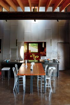 A custom recycled-Douglas fir table by VanEyk Custom Woodworks is the heart of the living-dining room. The double-height wall is clad in the same steel that wraps the exterior.