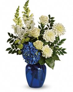 Ocean Devotion Bouquet - Blue, white and green flowers including blue hydrangea, white dahlias, white snapdragons, pale green roses and green button mums are arranged in a cobalt blue glass vase.
