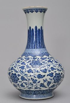 A MING-STYLE BLUE AND WHITE VASE, Mark And Period Of QianLong. The exterior of the vase is decorated with numerous blue colour lotus blossoms and ruyi clouds. The base of the vase has a blue marked seal. 13 3/8 in. tall.