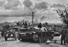 "Elements of SS Division ""Leibstandarte Adolf Hitler"" on the outskirts of Mariupol. Center assault gun StuG.III Ausf.B, left 105 mm light field howitzer leFH18, right background ACS Panzerjäger I."
