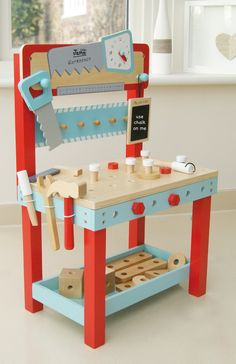 Designer Kids Wooden Toys - Indigo Jamm Little Carpenters Bench - An attractive colourful first work bench with 25 pieces that can be hammered, screwed and bolted!  Little Carpenter Bench is great for imaginative play!  Includes a wooden saw, spanner, hammer and screwdriver for hours of building fun. It also features a teaching clock with moving hands and mini chalkboard for very important notes and measurements!  #kidswoodentoys #christmasgifts #giftsforkids #littlebooteek
