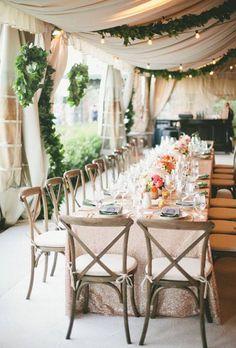 Garlands of greenery and lights dress up an open tent ~ http://www.brides.com/wedding-ideas/2015/09/wedding-tent-ideas
