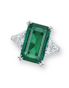 AN EMERALD AND DIAMOND RING, BY VAN CLEEF & ARPELS Set with a rectangular-shaped emerald weighing approximately 4.68 carats, flanked by shield-shaped diamonds, mounted in platinum, ring size 3½, in grey suede Van Cleef & Arpels case