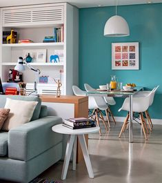 Paint colour can also help define areas of the home, especially in open-plan and compact spaces. This gorgeous turquoise wall, along with the bookshelf, accentuates the small dining area.