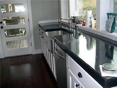 This poured in place top concrete countertop was created using a custom countertop mix with dry charcoal pigment integrally added. To enhance the color a water based black dye was rubbed into the surface. It was sealed using a solvent based sealer.
