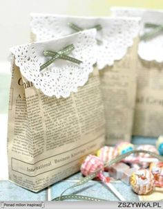 Shabby chic DIY gift sack made from newspaper and topped with folded round paper doily ribbon.